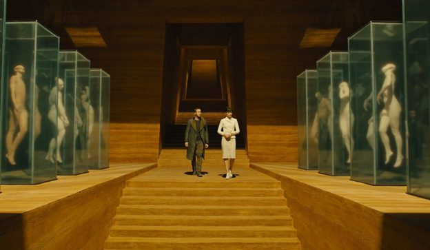 Ryan Gosling and Sylvia Hoeks walk past displays of replicants in Blade Runner 2049